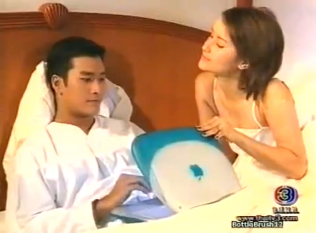 "A happy threesome: Ann Thongprasom, Au Tanakorn Posayanon, and an original 1999 ""clamshell"" iBook G3; from the 2001 สามี ตีตรา samee tee tra."