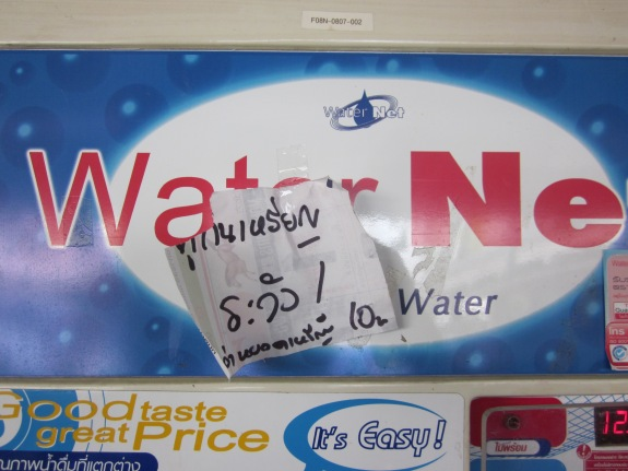 Handwritten Thai sign on water vending machine.